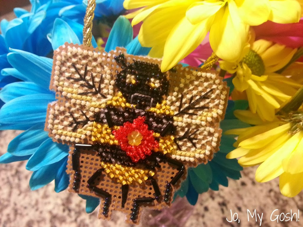 cross stitch of a bee that is finished with felt and ribbon